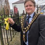 Photo of Mayor tying yellow ribbon at St Parts Church 23rd March 2021
