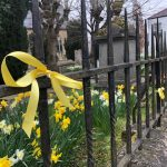 Photo of yellow ribbons tied to St Barts Church railings 23rd March 2021
